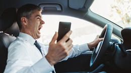 distracted driving: man yelling into cell phone while driving