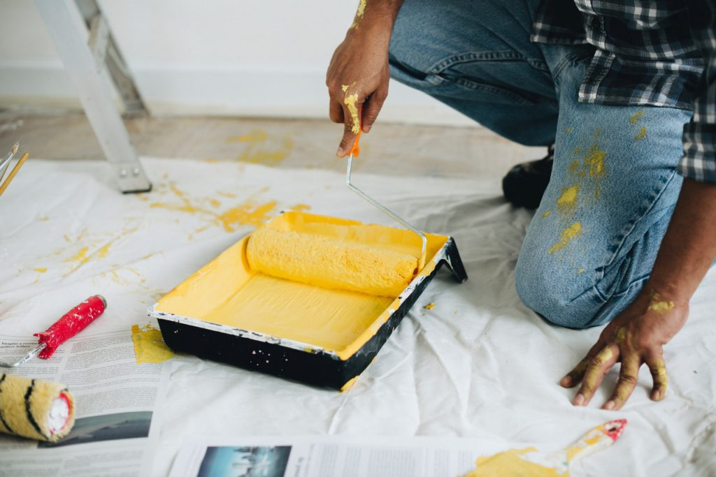 home contractor with roller in yellow paint, some spilled on floor