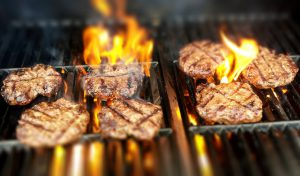 Sizzling burgers on a grill. Handle backyard fire responsibly.